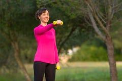 做重量的健康妇女训练户外在公园 库存照片