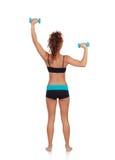 做重量的美丽的妇女定调子她的肌肉 免版税库存图片