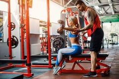 做重量的运动的女孩行使与她的个人教练员协助在健身房 免版税库存图片