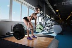 做重量级的锻炼的健身房的肌肉妇女 免版税图库摄影