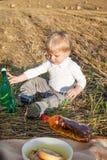 做野餐的两年的小小孩男孩在金黄干草领域 免版税库存图片