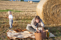 年轻做野餐的人和二个小男孩在干草领域 免版税库存照片
