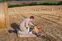 年轻做野餐的人和小男孩在干草领域 免版税库存图片