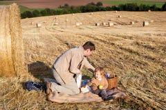 年轻做野餐的人和小男孩在干草领域 库存图片