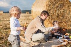 年轻做野餐的人和小男孩在干草领域 免版税库存照片