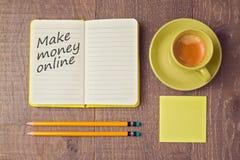 做金钱与笔记本和咖啡杯的网上概念 在视图之上 免版税库存照片