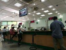 做银行业务交易的顾客在柜台 免版税库存图片
