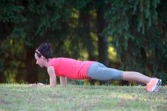 做铺板锻炼的亭亭玉立的美丽的运动女孩在公园 免版税库存照片