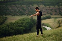 做锻炼用被举的手和看下来在自然风景背景的运动服的运动年轻人 免版税库存图片
