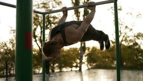做锻炼的年轻人户外在单杠户外 在垂悬在胳膊的平行的标志横线的女子柔软体操锻炼 股票视频