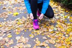 做锻炼的年轻体育妇女在秋天训练期间外面 免版税库存图片