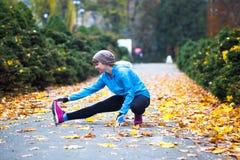 做锻炼的年轻体育妇女在秋天训练期间外面 库存图片