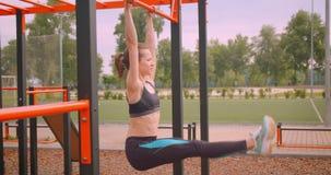 做锻炼的年轻俏丽的运动的健身女孩特写镜头画象在运动场在都市城市户外 影视素材