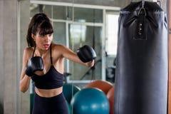 做锻炼的年轻健身女孩击中吊袋在一间把装箱的演播室健身房 运动服的妇女拳击手解决与手套的 图库摄影