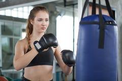 做锻炼的年轻健身女孩击中吊袋在一间把装箱的演播室健身房 运动服的妇女拳击手解决与手套的 库存图片