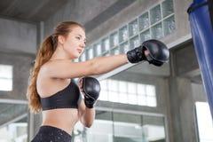 做锻炼的年轻健身女孩击中沙袋在boxi 免版税库存照片