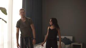 做锻炼的白种人夫妇在床附近,在他们早晨后醒了 做伸展运动的年轻夫妇 影视素材