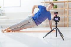 做锻炼的被集中的录影博客作者,当调查照相机时 免版税库存图片