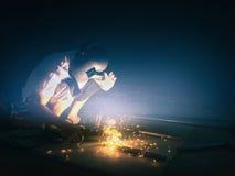 做闪闪发光的焊工,当工作时 行业概念 库存照片