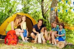 做阵营火的家庭画象在森林 免版税库存图片