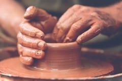 做陶瓷罐的陶瓷工在瓦器轮子 免版税库存图片