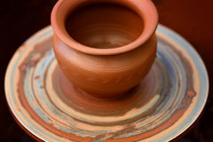 做陶瓷罐的陶瓷工在瓦器轮子 免版税图库摄影