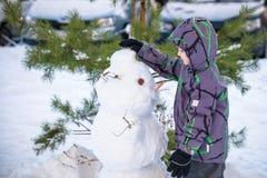 做雪人和吃红萝卜的滑稽的小孩男孩,使用获得与雪的乐趣,户外在冷的天 活跃休闲childr 免版税库存照片