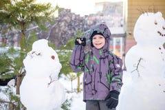 做雪人和吃红萝卜的滑稽的小孩男孩,使用获得与雪的乐趣,户外在冷的天 活跃休闲childr 库存照片