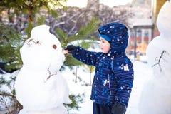 做雪人和吃红萝卜的滑稽的小孩男孩,使用获得与雪的乐趣,户外在冷的天 活跃休闲childr 库存图片