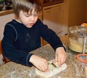 做雪人曲奇饼的愉快的男孩 免版税图库摄影