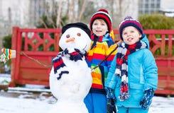 做雪人的两个小兄弟姐妹男孩 免版税库存照片