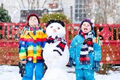 做雪人的两个小兄弟姐妹男孩 图库摄影