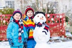 做雪人的两个小兄弟姐妹男孩 免版税图库摄影