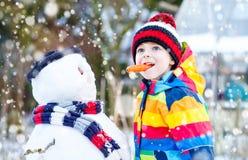 做雪人的五颜六色的衣裳的滑稽的孩子男孩,户外 免版税库存图片