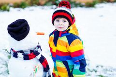 做雪人的五颜六色的衣裳的滑稽的孩子男孩,户外 免版税库存照片