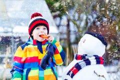 做雪人的五颜六色的衣裳的滑稽的孩子男孩,户外 库存图片