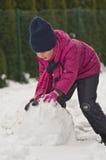 做雪人的女孩 免版税库存图片