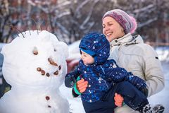 做雪人的小小孩男孩户外在美好的冬日 免版税图库摄影