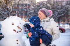 做雪人的小小孩男孩户外在美好的冬日 免版税库存照片