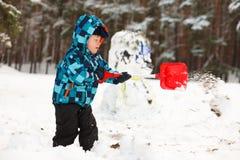 做雪人的小男孩 库存照片