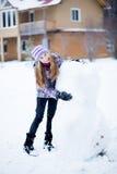 做雪人的少年女孩户外在房子前面 免版税库存照片