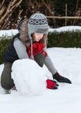 做雪人的少年女孩 免版税库存照片