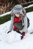做雪人的少年女孩 库存图片