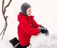 做雪人的微笑的男孩。 库存图片