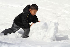 做雪人的日本男孩 免版税库存照片