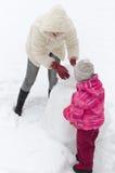 做雪人的母亲和子项 图库摄影