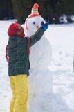 做雪人的男孩在冬天 库存照片