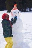 做雪人的男孩在冬天 免版税库存图片