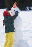 做雪人的男孩在wintwr 免版税库存照片
