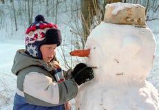 做雪人的男孩 库存照片